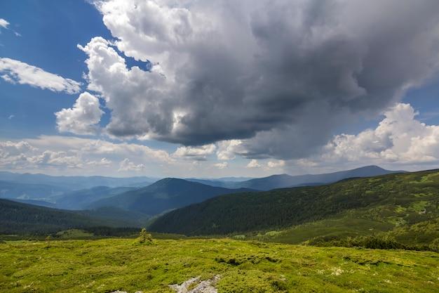 Oświetlone porannym słońcem szeroka zielona dolina, wzgórza pokryte lasem i odległe mgliste góry pod jasnym błękitnym letnim niebem i białymi obłokami chmur. piękno przyrody, turystyki i koncepcji podróży.