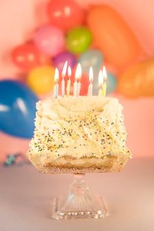 Oświetlone świeczki nad ciastem nad cakestand