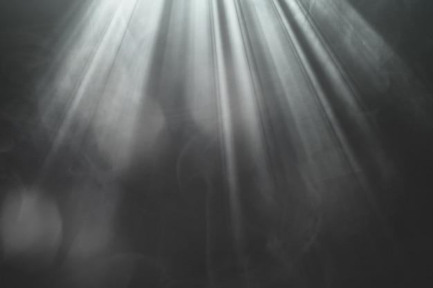 Oświetlone złote promienie reflektorów na scenie na czarnym tle