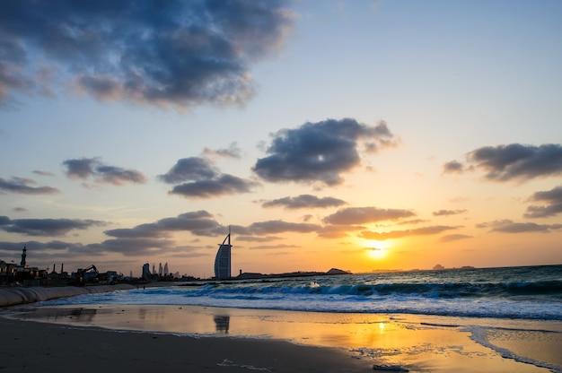 Oświetlony burj al arab i jumeirah beach hotel o zachodzie słońca.