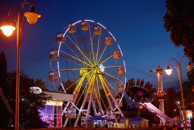 Oświetlony diabelski młyn w parku rozrywki w nocy miasto