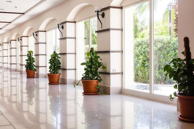 Oświetlony długi korytarz w nowoczesnym budynku biurowym z panoramicznymi oknami