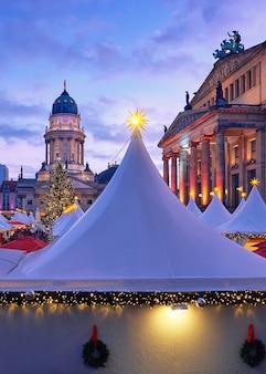 Oświetlony jarmark bożonarodzeniowy gandarmenmarkt w berlinie o zachodzie słońca