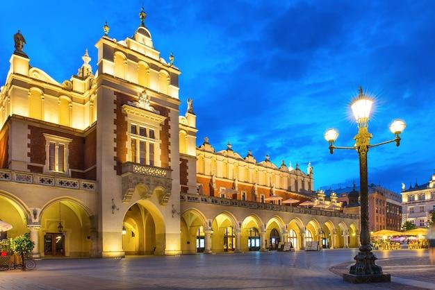 Oświetlony pałac na rynku starego miasta nocą z ciemnoniebieskim niebem. kraków, polska
