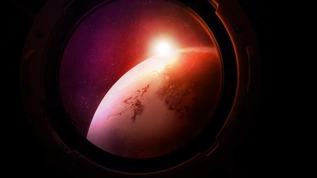 Oświetlony słońcem mars z okrągłego iluminatora statku kosmicznego.