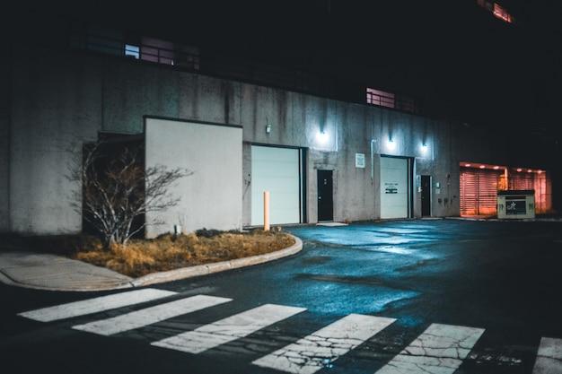 Oświetlony szary budynek od strony pieszego