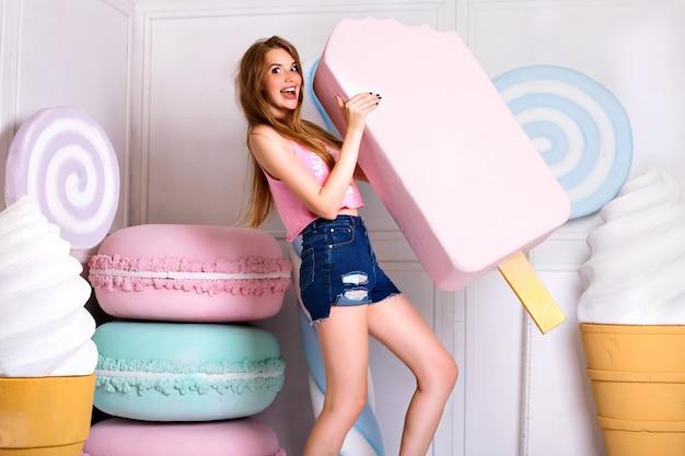 Oszałamiająca atrakcyjna blondynka trzyma duże rekwizyty różowe lody. ubrana w stylowy, jasny podkoszulek i modne szorty.