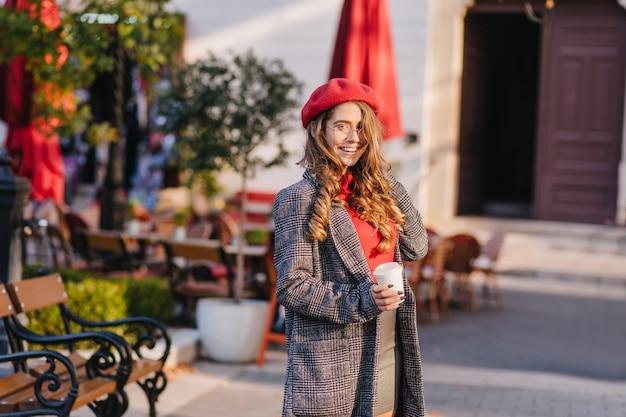 Oszałamiająca biała dziewczyna w długim płaszczu pije kawę podczas spaceru w parku