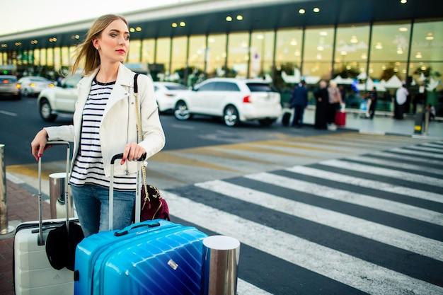 Oszałamiająca blondynka dama z niebieskimi i białymi walizkami stoi przed przejściem na ulicę