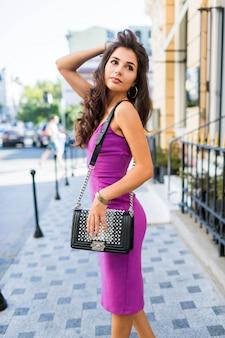Oszałamiająca brunetka dziewczyna spacerująca po słonecznej ulicy, ciesząc się słoneczną pogodą, robiąc zakupy, czekając na przyjaciół, aby spędzić miło czas w weekendy. falowana fryzura. fioletowa, aksamitna seksowna sukienka. romantyczny nastrój.