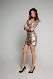 Oszałamiająca brunetka kobieta w złotej błyszczącej sukni i szpilkach.