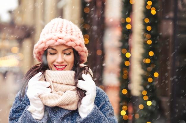 Oszałamiająca brunetka ma na sobie jasnoróżową czapkę z dzianiny i szalik, spacerując po mieście podczas opadów śniegu. miejsce na tekst