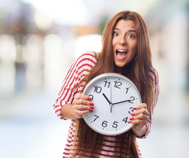 Oszałamiająca brunetka z zegarem w ręce.