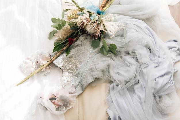 Oszałamiająca delikatna suknia ślubna z koralikami i koronką leży obok bukietu proteus. poranek panny młodej