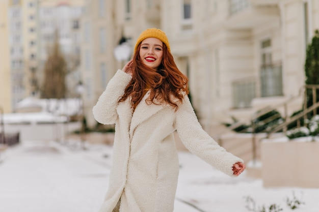 Oszałamiająca długowłosa dziewczyna w żółtym kapeluszu pozuje na rozmycie ulicy. odkryty strzał szczęśliwy damy imbir, ciesząc się zimą.