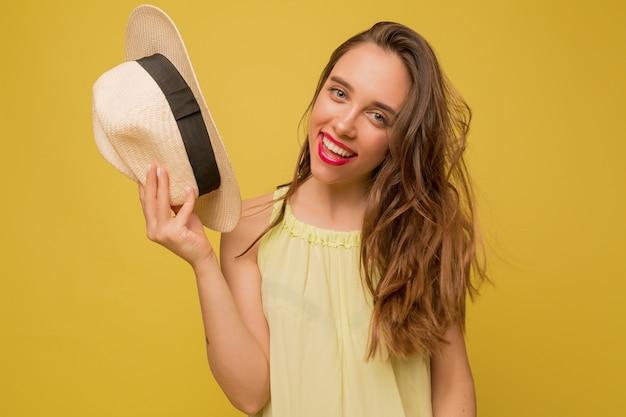 Oszałamiająca długowłosa modelka pozuje na żółtej ścianie, trzyma kapelusz i uśmiecha się