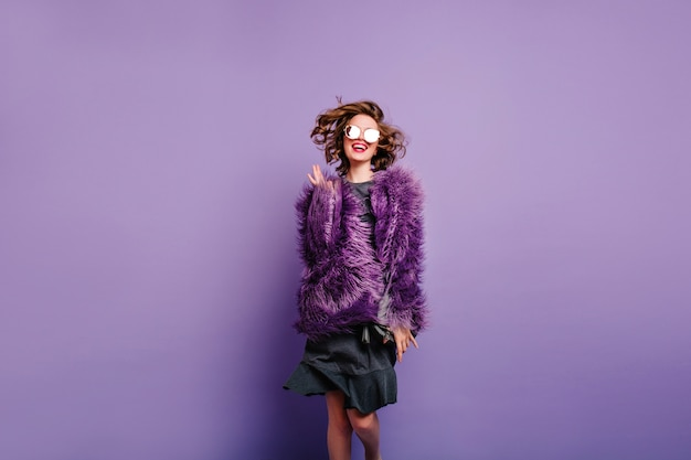 Oszałamiająca dziewczyna w dobrym nastroju skacząca na fioletowym tle i uśmiechnięta