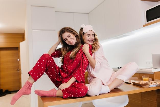Oszałamiająca dziewczyna w różowej piżamie obejmując przyjaciela po śniadaniu. kryty zdjęcie śmiechu szczęśliwa dziewczyna w czerwonej piżamie siedzi na stole w kuchni.