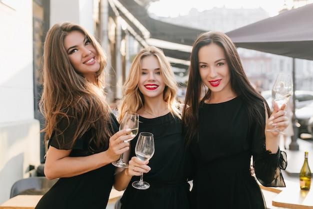 Oszałamiająca elegancka kobieta z czarnymi długimi włosami spędzająca czas z siostrami w mieście
