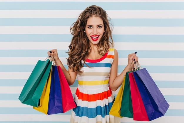 Oszałamiająca europejska kobieta kupuje letnie ubrania. portret czarującej modelki z nowymi zakupami.