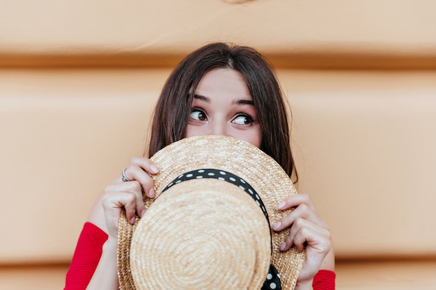 Oszałamiająca kaukaski kobieta z letnim kapeluszem w rękach, wygłupiać się na świeżym powietrzu. brunetka dama z wyrazem twarzy szczęśliwy pozowanie przed ścianą.
