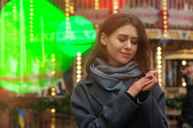 Oszałamiająca kobieta nosi szary płaszcz spacerując po ulicy w świetle bokeh. pusta przestrzeń