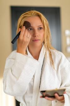 Oszałamiająca kobieta stojąca przed lustrem stosowania makijażu