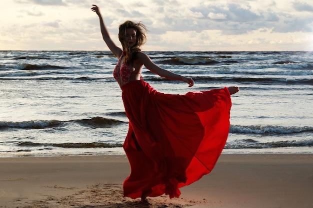 Oszałamiająca kobieta ubrana w piękną czerwoną sukienkę na plaży w czasie zachodu słońca