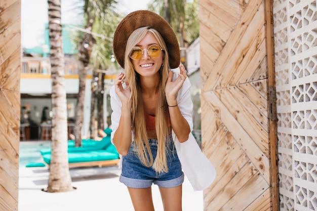 Oszałamiająca kobieta w pomarańczowych okularach przeciwsłonecznych podczas letniej sesji zdjęciowej w ośrodku. urocza kaukaski kobieta z długimi blond włosami pozuje przed leżakami.