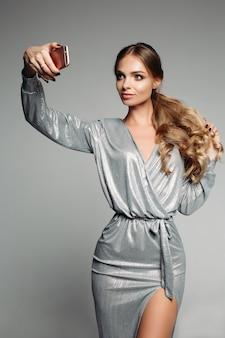 Oszałamiająca kobieta w srebrnej wieczorowej sukience z długimi falującymi włosami tak