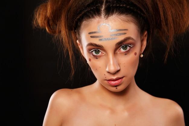 Oszałamiająca kobieta wygląda jak baran z ciemnym makijażem i odciskami na twarzy
