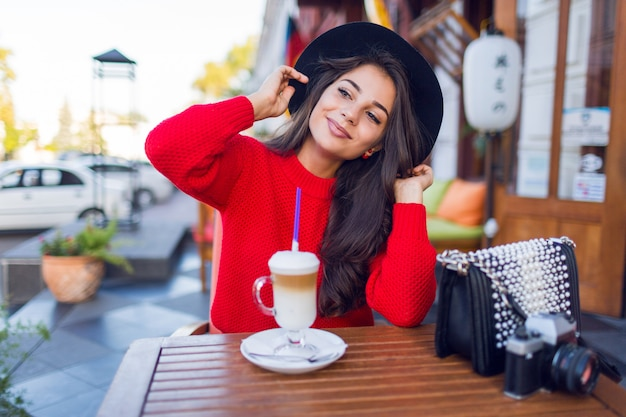 Oszałamiająca młoda dama w stylowym czarnym kapeluszu i jaskrawoczerwonym swetrze siedzi w otwartej kawiarni i pije kawę z mlekiem lub cappuccino.