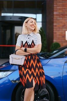 Oszałamiająca młoda kobieta wojująca sukienka pozuje przed swoim samochodem na zewnątrz, kierowca właściciel