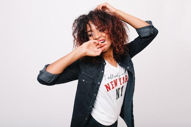 Oszałamiająca młoda kobieta z krótką fryzurą zmysłowo pozuje z zadowolonym wyrazem twarzy. kryty portret entuzjastycznej afrykańskiej dziewczyny z brązowymi kręconymi włosami, odwracając wzrok z uśmiechem.