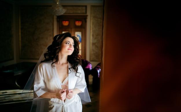 Oszałamiająca panna młoda brunetka otwiera jej jedwabną szatę, podczas gdy ona pozuje w pokoju