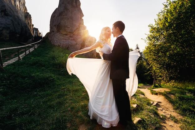 Oszałamiająca para patrzy sobie w oczy stojąc na skałach