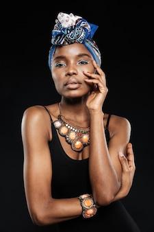 Oszałamiająca piękna młoda stylowa czarna kobieta odizolowana na czarnej ścianie