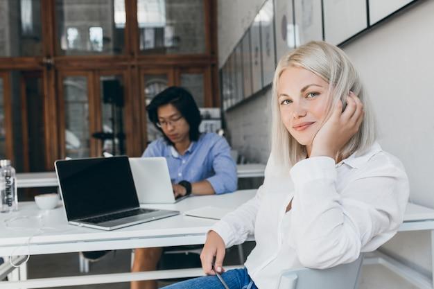 Oszałamiająca programistka bawiąca się blond włosami podczas pozowania w miejscu pracy z kolegą z azji. zapracowany chiński programista pracujący z laptopem siedzący przy stole z białą sekretarką.