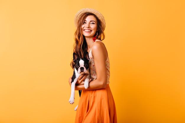 Oszałamiająca ruda dziewczyna w letnim stroju trzyma buldoga francuskiego. atrakcyjna młoda dama w kapeluszu śmiejąca się podczas sesji portretowej ze szczeniakiem.