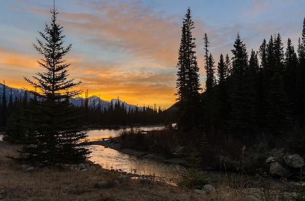 Oszałamiająca sceneria wschodu słońca nad rzeką bow i górami zamkowymi w parku narodowym banff w albercie, kanada