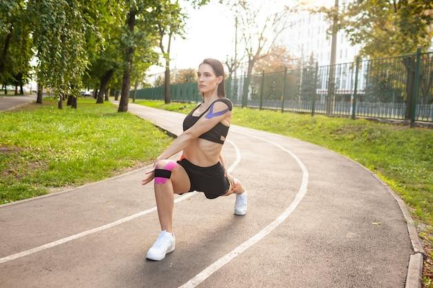 Oszałamiająca sprawna dziewczyna ubrana w czarny strój sportowy szkolenia w letnim parku