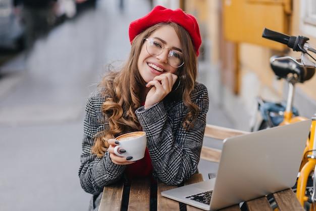 Oszałamiająca studentka pracuje z laptopem w kawiarni na świeżym powietrzu w zimny jesienny poranek