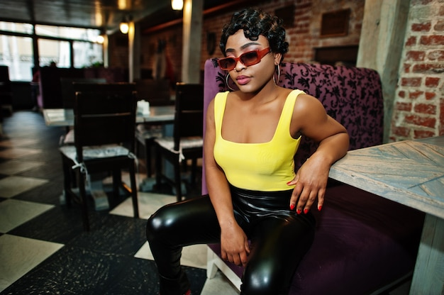 Oszałamiające afroamerykanki w żółtym topie i czarnych skórzanych spodniach pozują w pubie.
