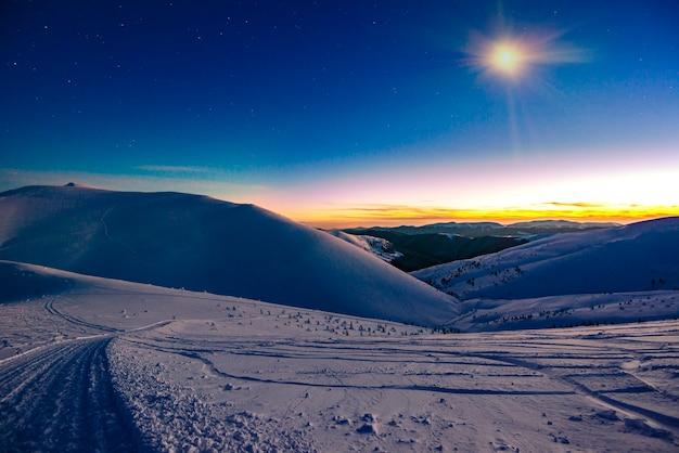 Oszałamiające piękne widoki na stoki w ośrodku narciarskim po zachodzie słońca późnym wieczorem