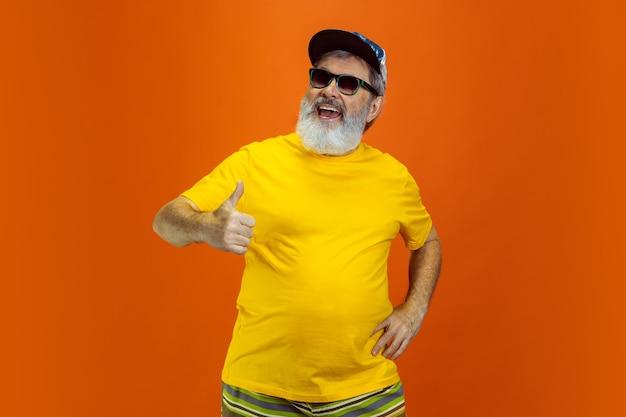 Oszałamiające pozowanie, kciuk w górę. portret starszego hipster człowieka w okulary na białym tle na pomarańczowym tle studio. koncepcja tech i radosny starszy styl życia. modne kolory, wieczna młodość. copyspace dla twojego a