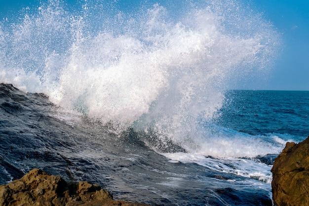 Oszałamiające ujęcie szalonych, potężnych fal morskich rozbijających formacje skalne