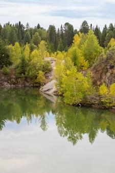 Oszałamiające zdjęcie jesiennych liści odbijanych w jeziorze z lustrzaną powierzchnią wody.