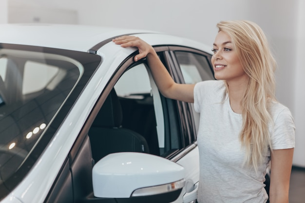 Oszałamiająco kobieta patrzeje daleko od stojący blisko jej nowego samochodu przy przedstawicielstwem handlowym.