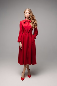 Oszałamiająco smukły model w jasnoczerwonej sukience i czarnych obcasach.