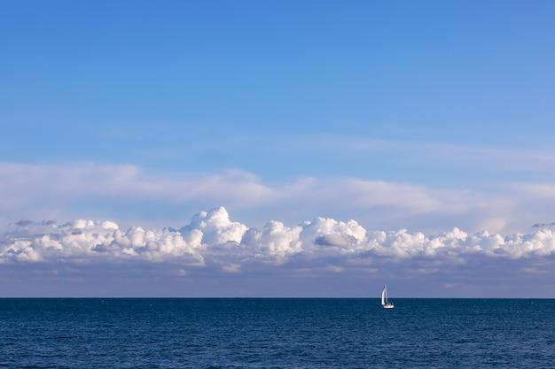 Oszałamiający krajobraz morski z żaglówką i wieczornym niebem z teksturowanymi chmurami.